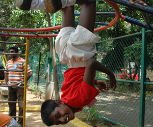 boy hanging upside down in playground