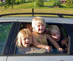 group of children looking out a car window