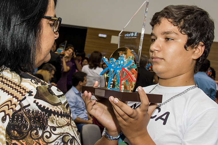 Representing children and adolescents from his municipality, Francisco, 14, gives the UNICEF Municipal Seal of Approval trophy to the mayor of Florânia, in state of Rio Grande do Norte (December, 2016).